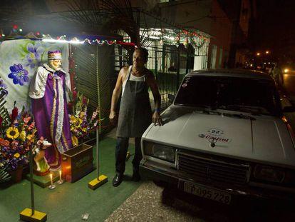 Anselmo Ramírez, en su casa de La Habana junto a la imagen de San Lázaro y su Lada ruso, el pasado 16 de diciembre.