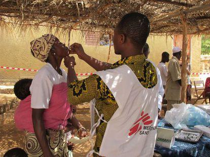 Un cooperante de Médicos sin Fronteras vacuna a una mujer en Guinea Conakry durante una epidemia de cólera.