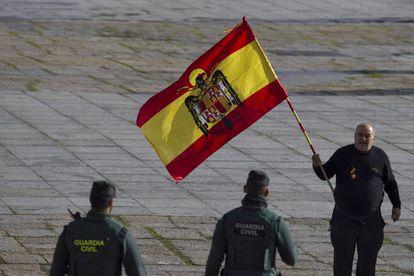 Agentes de la Guardia Civil se disponen a quitar una bandera preconstitucional a uno de los asistentes al Valle de los Caídos.