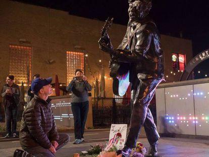 Pie de Foto: Brad Pierce enciende una vela ante la estatua de Chuck Berry en University City, en EE UU.