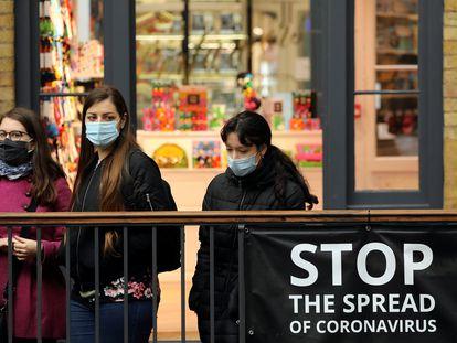 Vecinos de Londres, protegidos con mascarillas, en el exterior del Convent Garden.