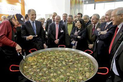 El presidente valenciano, Francisco Camps, prueba una paella durante su visita, ayer, a la feria Fruit Logística de Berlín.