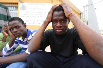 Un grupo de inmigrantes subsaharianos sentados frente a la puerta del CETI de Melilla.