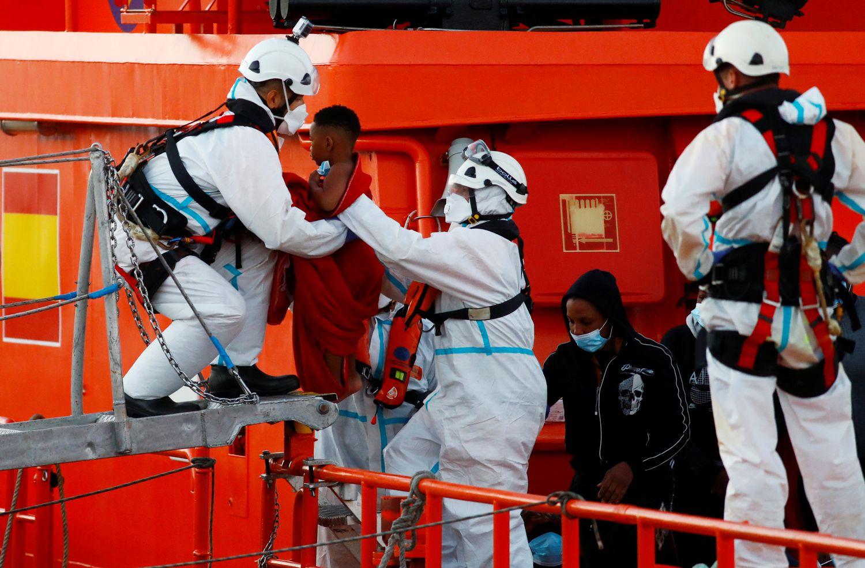 Un miembro de la Cruz Roja ayuda a bajar del barco a un niño en el puerto de Arguineguín (Gran Canaria) este miércoles.