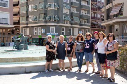 Isabel Matute y Marisol Pérez (4ª y 5ª desde la der.), con otras seis aparadoras de la asociación, al lado de la estatua que representa el sector en Elche.