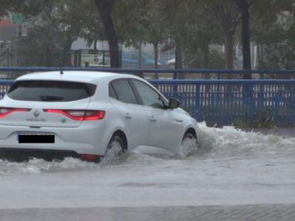Un coche avanza por una calle de València inundada tras las fuertes lluvias caídas en las últimas horas en el litoral.