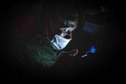 Un inmigrante consulta su teléfono en el campamento de Las Raíces, en Tenerife, en marzo de 2021.