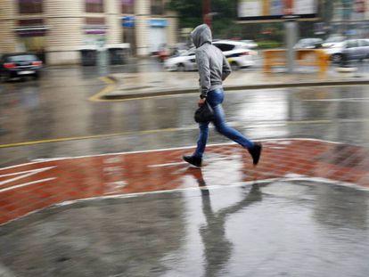 Un joven corre bajo la lluvia en Valencia.