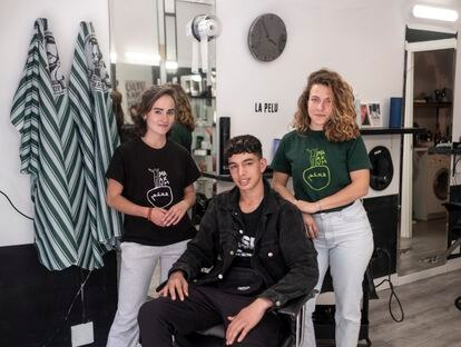 El joven marroquí Hicham, que acaba de cumplir 18 años, posa en la peluquería de Getafe junto a Joana y Elena, miembros de la asociación Maakum.