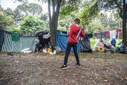 Un niño juega béisbol en el campamento improvisado por migrantes venezolanos en el separador de la autopista norte.