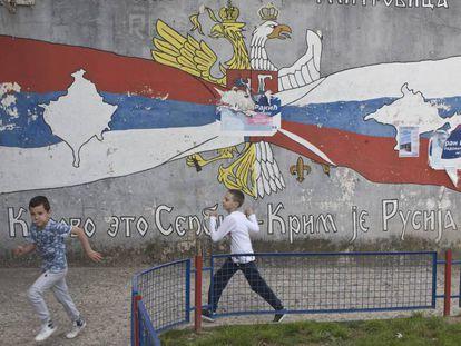 Niños jugando delante de un mural frente a símbolos serbios y rusos en el norte de Mitrovica, la zona en la que viven los serbios. El sur es la parte en la que viven los albanokosovares.