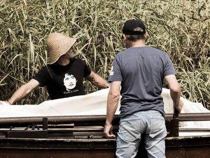 Dos participantes en la remontada del río Ulla en honor a Rosalía de Castro preparan su embarcación.