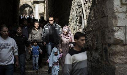 Fieles palestinos caminan junto a soldados armados en la Ciudad Vieja de Jerusalén, el viernes