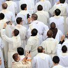 Los sacerdotes se toman fotos con sus móviles durante la misa oficiada por el Papa Francisco antes de la apertura de la Puerta Santa.