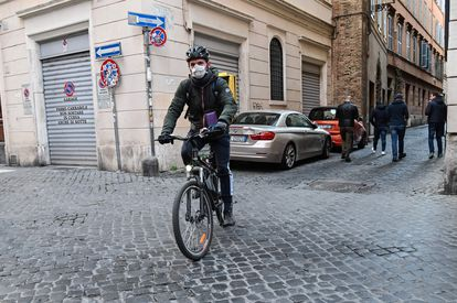 Un mensajero con mascarilla circula por Roma, este miércoles.