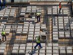 Sevilla/28-07-2021: Daniel Cordero (chaleco naranja), gruista en la construcción, junto a una sombrilla y un dispensador de garrafas de agua ubicadas en la zona de trabajo.FOTO: PACO PUENTES/EL PAIS