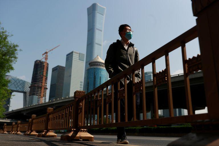 Un hombre, con mascarilla, camina por Beijing, China, este viernes.