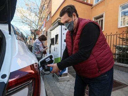 Unos usuarios intentando recargar su vehículo en un punto de recarga de coches eléctricos  en la Ronda de Valencia (Madrid).