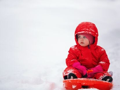 Un niño juega con su trineo en la nieve.