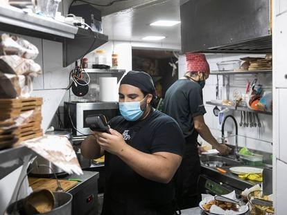 Trabajadores en el restaurante de comida venezolana El rincon de la Abuela Venezolana, durante la recepción de un pedido.