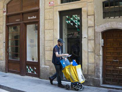 Un cartero pasa por delante de un bajo comercial en una calle de Barcelona.