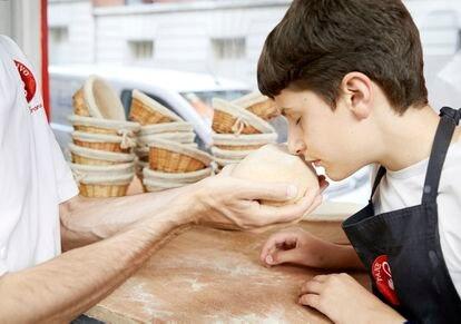 Adriano Farano le da a su hijo Lorenzo masa de pan para oler en su panadería Pane Vivo en París.
