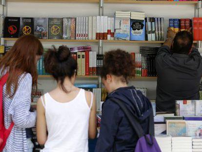 Un grupo de jóvenes examina libros en una caseta de la feria de Valencia.