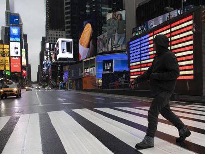 Un hombre cruza Times Square, en Nueva York, donde el alcalde ha pedido a los ciudadanos que se queden en casa para evitar la propagación del coronavirus.