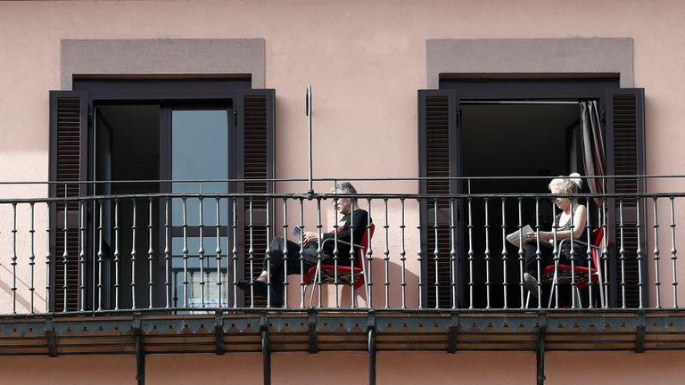 Dos personas leen en el balcón de su domicilio tras el estado de alarma decretado en España.