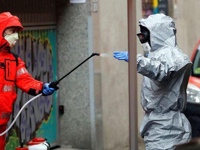 Un bombero de Barcelona desinfecta a un compañero tras salir de la residencia de religiosas del Colegio Sant Josep, donde hay varios casos de Covid-19.
