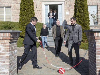 Puigdemont retira la cadena de la entrada de su casa de Waterloo, en febrero de este año.
