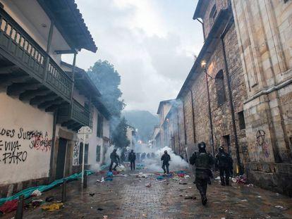 Policías antidisturbios lanzan gases y caminan entre escombros tras las protestas del 21 de noviembre de 2019.