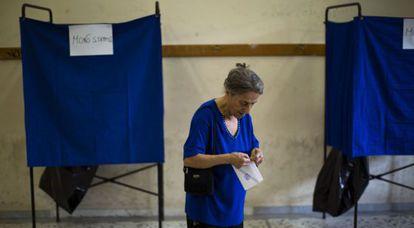 Una mujer sostiene su papeleta antes de votar, en Atenas.