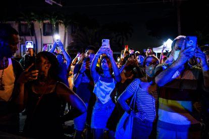 Un grupo de personas graban con sus móviles la demolición del edificio.
