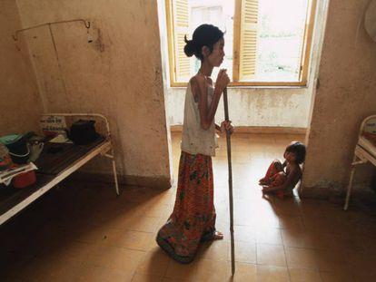 Una mujer con VIH usa un bastón para caminar hacia su cama de un hospital de Camboya.