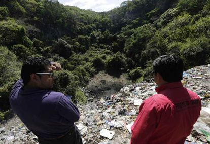 Dos personas observan el basurero de Cocula, Guerrero