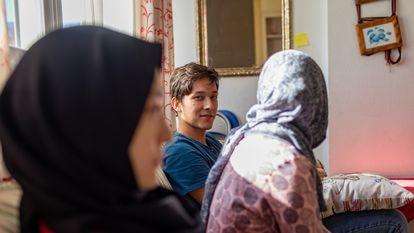 El joven afgano Hujjat, junto a dos de sus hermanas, en el piso de acogida donde vive con toda su familia en España.