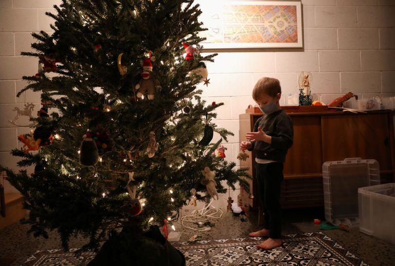 Un niño con mascarilla decora un árbol de Navidad en Nueva York.