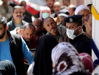 Un policía hace guardia mientras los habitantes esperan fuera de un banco, en la ciudad de Gaza, el pasado 29 de marzo.