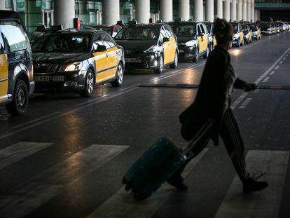 Una usuaria del aeropuerto de Barcelona cruza frente a los taxis de la T1.
