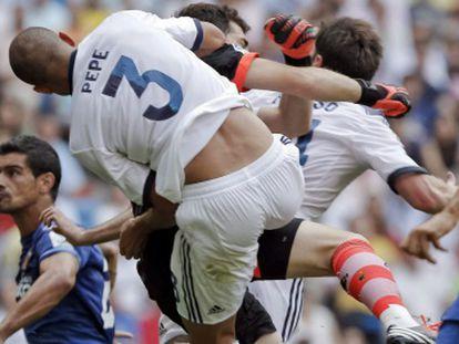 Casillas choca con Pepe en su intento por despejar.