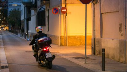 Una motocicleta circula por una calle del barrio de Sants.