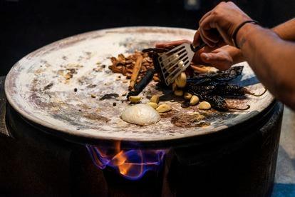El jefe de cocina de Pujol, Alex Bremont tuesta los ingredientes en un comal de barro.