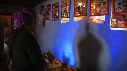 Lucia Santos Coyoi mira las fotos de su hijo colgadas en la pared de su casa.