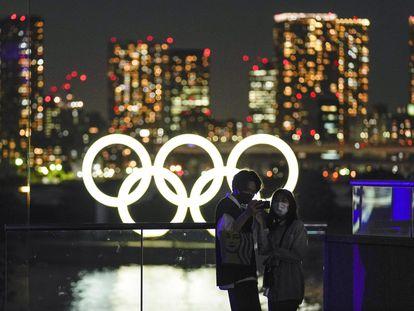 Una pareja se toma un selfi antes los anillos olímpicos en Tokio.
