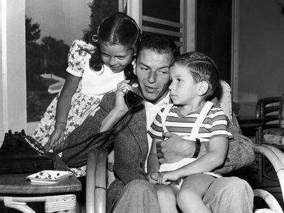 Frank Sinatra habla por teléfono junto a sus hijos, Nancy y Frank Jr., en Los Ángeles (EE UU) en 1948.