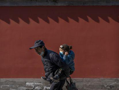 Un abuelo pasea con su nieto por un parque de Pekín, el pasado febrero.