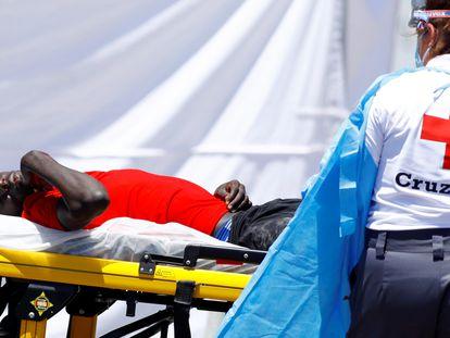 Un migrante es trasladado a una ambulancia,en el puerto de Arguineguín (Gran Canaria), el jueves.
