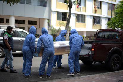 Trabajadores de una funeraria transportan el cuerpo de un hombre muerto en Guayaquil, Ecuador, este miércoles.