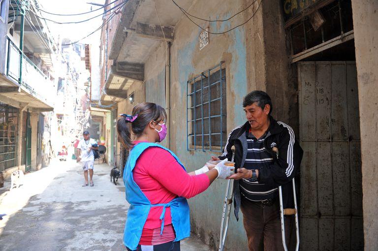 Una militante de Barrios de Pie reparte comida a un habitante de la villa 1-11-14 considerado grupos de riesgo ante la covid-19